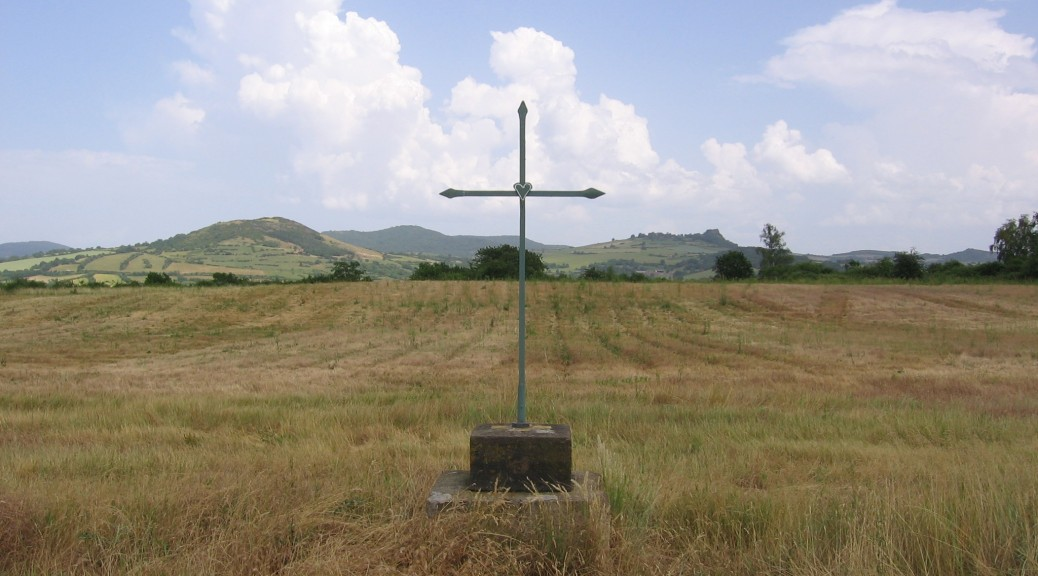 A cross marker in a field in France.